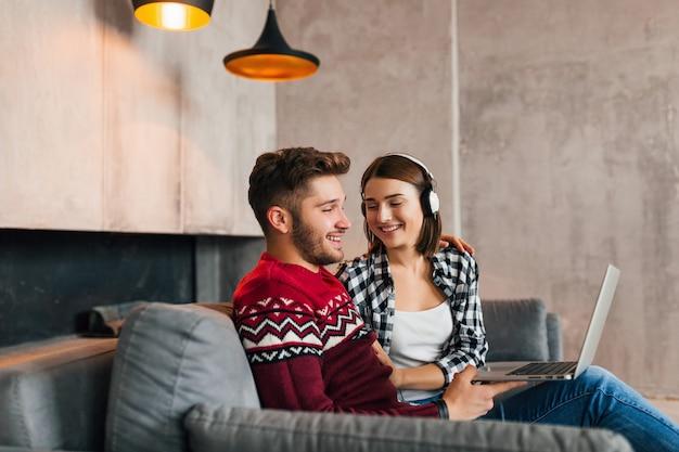 Giovane uomo sorridente e donna seduta a casa in inverno, lavorando al computer portatile, ascoltando le cuffie, coppia nel tempo libero trascorrendo del tempo insieme, libero professionista, felice, incontri