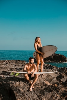 Young smiling man and woman with surf boards on rock near sea