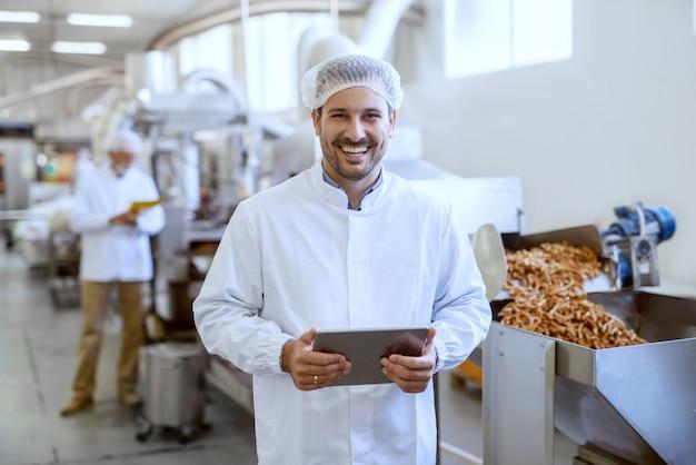 Молодой улыбающийся менеджер в стерильной форме держит таблетку и смотрит в камеру, стоя на пищевой фабрике.