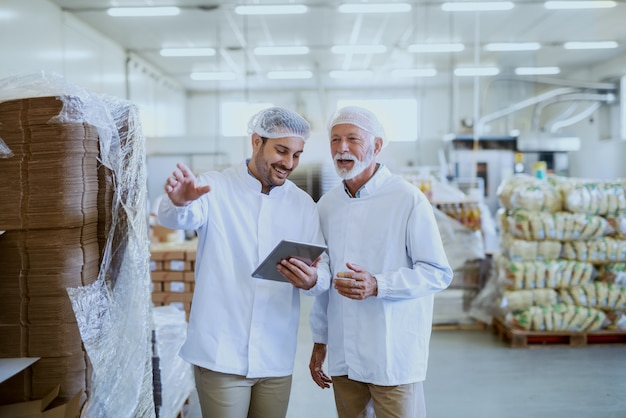 Молодой улыбающийся менеджер в стерильной форме с помощью планшета для проверки товаров и разговора с сотрудником. интерьер пищевой фабрики.
