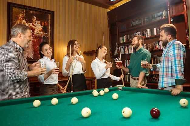 Молодые улыбающиеся мужчины и женщины, играющие в бильярд в офисе или дома после работы.