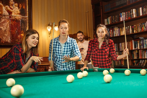 Young smiling men and women playing billiards at office or home after work. business colleagues involving in recreational activity. friendship, leisure activity, game concept.