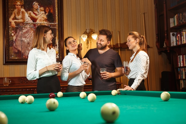 Young smiling men and women playing billiards at office or home after work. business colleagues involving in recreational activity.