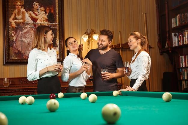 Giovani uomini e donne sorridenti che giocano a biliardo in ufficio oa casa dopo il lavoro. colleghi di lavoro coinvolti in attività ricreative.