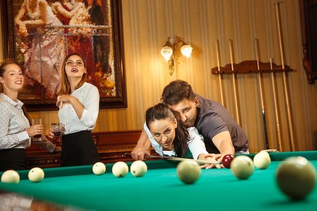 Giovani uomini e donne sorridenti che giocano a biliardo in ufficio oa casa dopo il lavoro. colleghi di lavoro coinvolti in attività ricreative