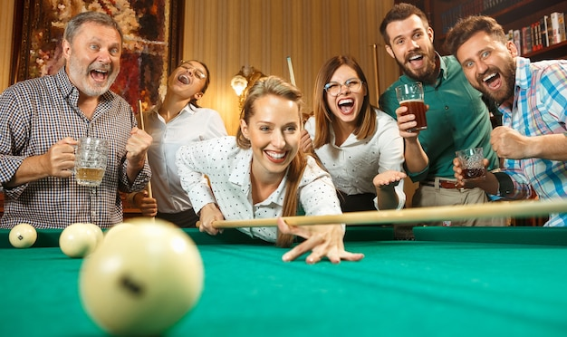Young smiling men and women playing billiards at office or home after work. business colleagues involving in recreational activity
