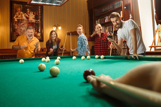 Young smiling men and women playing billiards at office or home after work