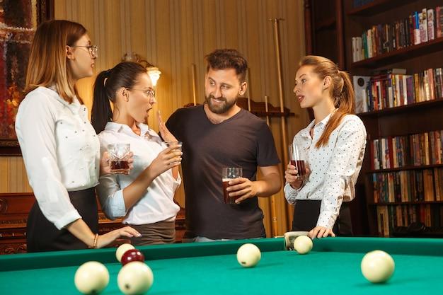 Giovani uomini e donne sorridenti che giocano a biliardo in ufficio oa casa dopo il lavoro.