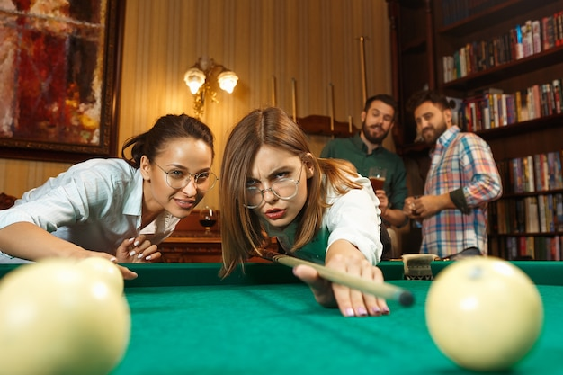 Young smiling men and women playing billiards at office or home after work.