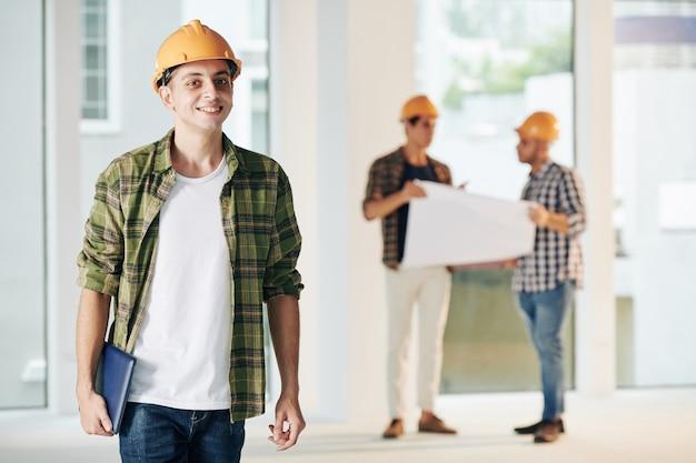 彼のチームと一緒にインテリア仕上げに取り組んでいる格子縞のシャツを着た若い笑顔の中東の建設エンジニア