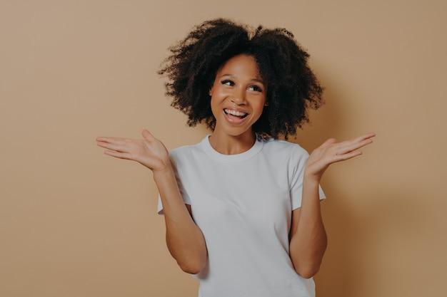 Молодая улыбающаяся кудрявая женщина смешанной расы, нерешительно поднимающая обе руки и смотрящая в сторону, принимая решение или выбирая что-то, одетая в белую футболку, изолированную на бежевом фоне