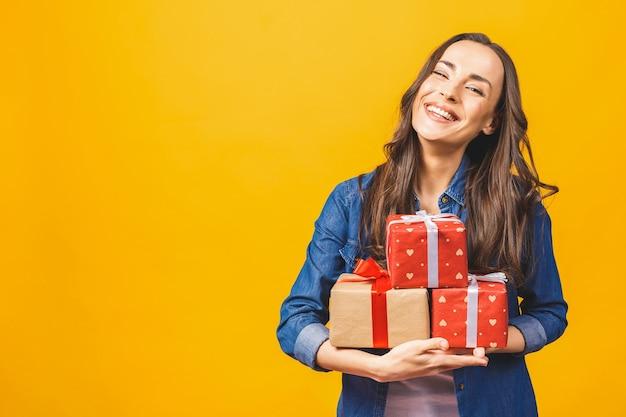 Молодая улыбающаяся модель держит подарочную коробку