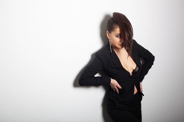 トレンディなジャケットのスーツを着ている若い笑顔のモデルは、ファッションポーズで彼女の長く美しい健康な髪を示しています