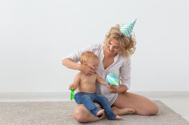 でカーペットの上で一緒に時間を過ごす誕生日の帽子の若い笑顔の母とかわいい娘
