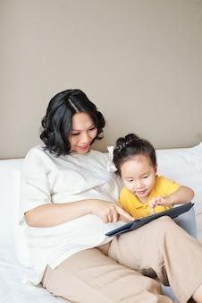Молодая улыбающаяся мать и ее маленькая дочь играют в игру на планшетном компьютере