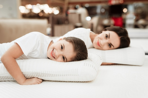 Young smiling mother and little girl on mattress