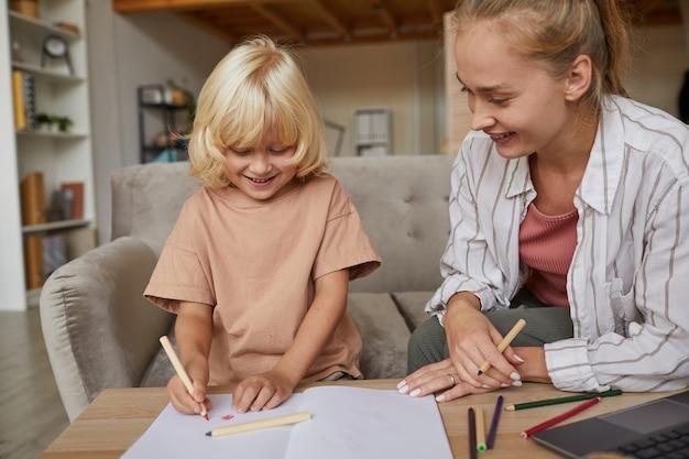 部屋のテーブルで描くように教えている息子の写真を見ている若い笑顔の母親