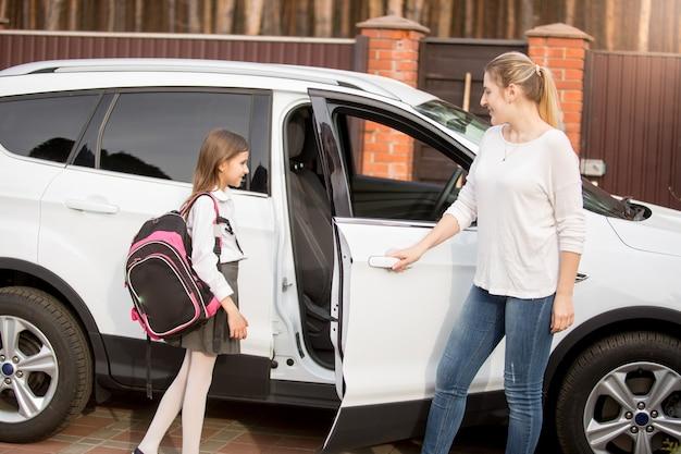 Молодая улыбающаяся мать встречает дочь после школьных уроков
