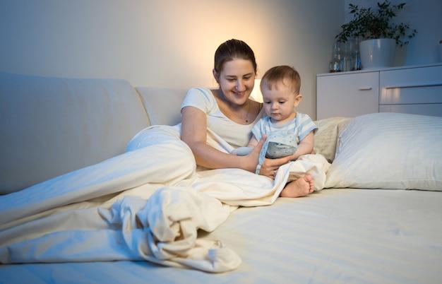 人形で夜に赤ちゃんと遊ぶ若い笑顔の母親