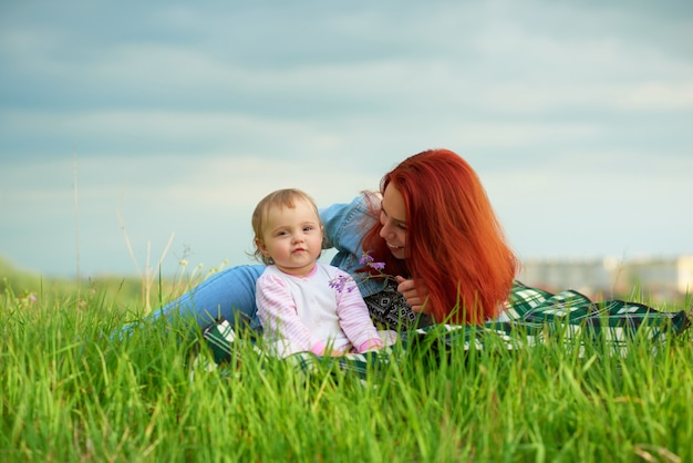 Young smiling mother playing with her little daughter laying on grass.