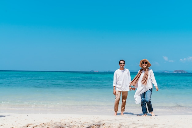 Young smiling muslim couple holding hands on the beach in vacation day.
