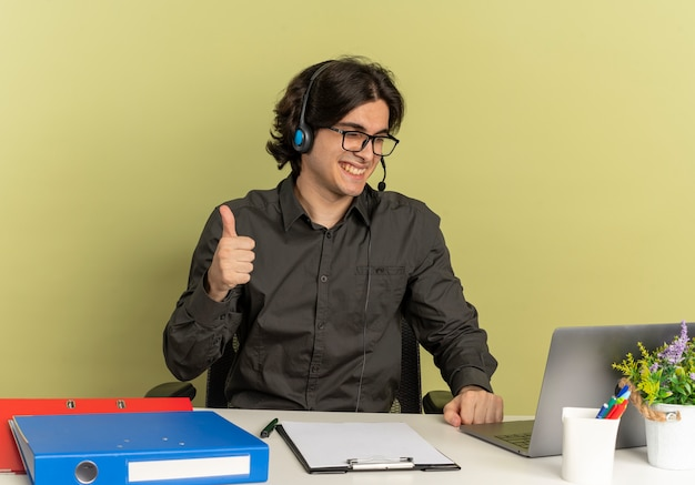 Young smiling office worker man on headphones in optical glasses sits at desk with office tools using and looking at laptop thumbs up
