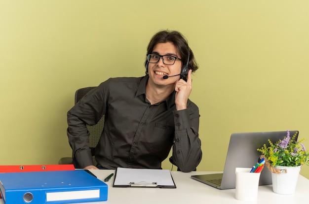 광학 안경에 젊은 미소 회사원 남자 노트북을 사용하는 사무실 도구와 책상에 앉아 복사 공간이 녹색 배경에 고립 된 헤드폰에 손을 넣습니다