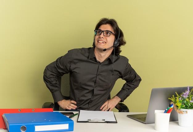 광학 안경에 헤드폰에 젊은 웃는 회사원 남자 노트북을 사용하는 사무실 도구와 책상에 앉아 복사 공간이 녹색 배경에 고립 된 측면에서 보인다