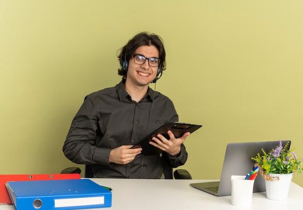 광학 안경에 헤드폰에 젊은 웃는 회사원 남자는 복사 공간이 녹색 배경에 고립 된 클립 보드를 들고 노트북을 사용하는 사무실 도구와 책상에 앉아