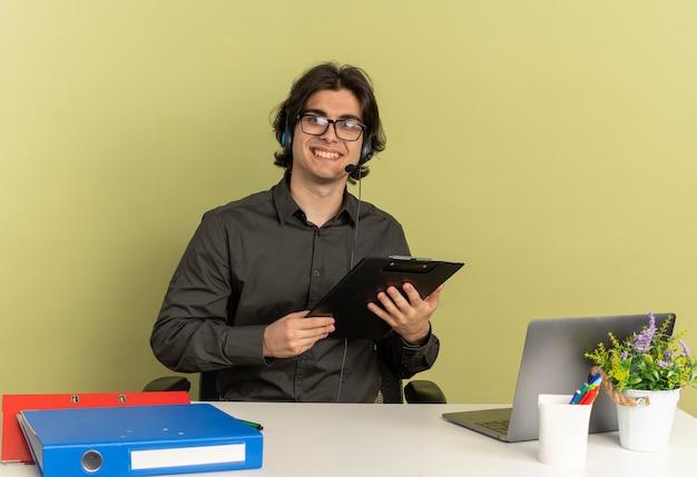 광학 안경에 헤드폰에 젊은 웃는 회사원 남자 노트북을 사용하는 사무실 도구와 책상에 앉아 복사 공간이 녹색 배경에 고립 된 카메라를보고 클립 보드를 보유