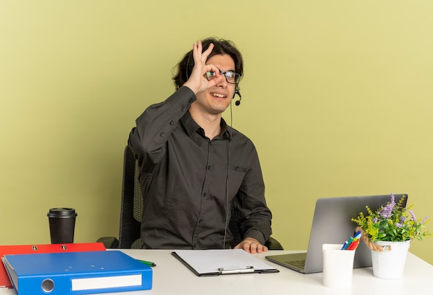 광학 안경에 헤드폰에 젊은 웃는 회사원 남자는 복사 공간이 녹색 배경에 고립 된 손가락을 통해 노트북을 사용하는 사무실 도구와 책상에 앉아
