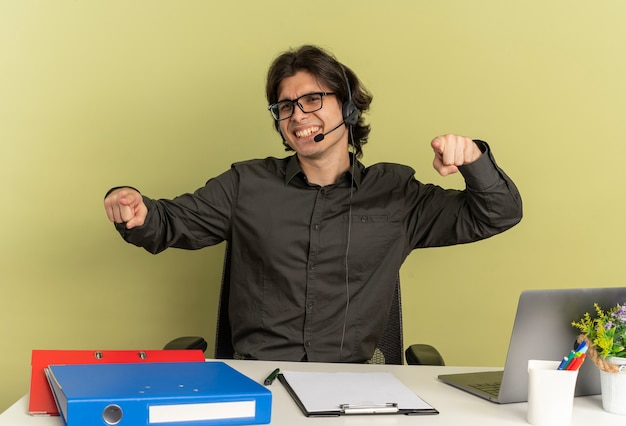 광학 안경에 헤드폰에 젊은 웃는 회사원 남자 노트북 포인트를 사용하여 사무실 도구와 책상에 앉아 복사 공간이 녹색 배경에 고립 된 카메라를 찾습니다