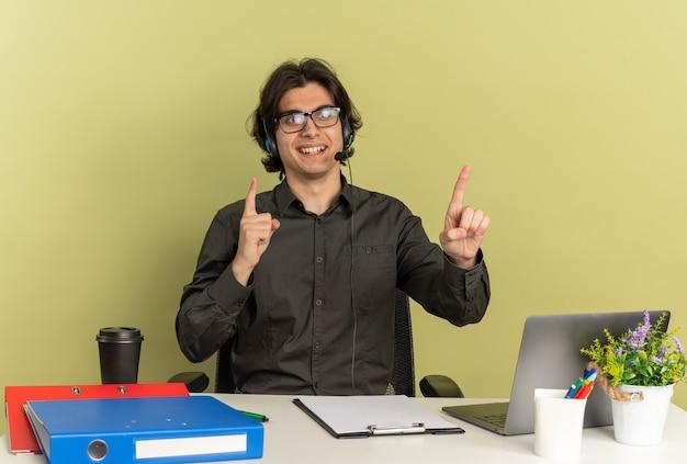 광학 안경에 헤드폰에 젊은 웃는 회사원 남자는 복사 공간이 녹색 배경에 고립 된 노트북 포인트를 사용하는 사무실 도구와 책상에 앉아