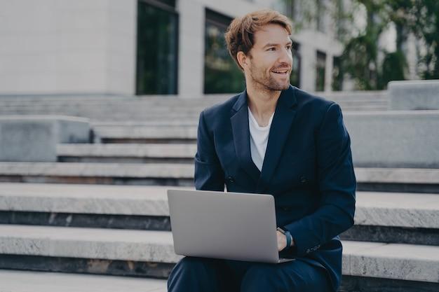 Молодой улыбающийся офисный работник сидит снаружи на лестнице в центре города, держа ноутбук на коленях