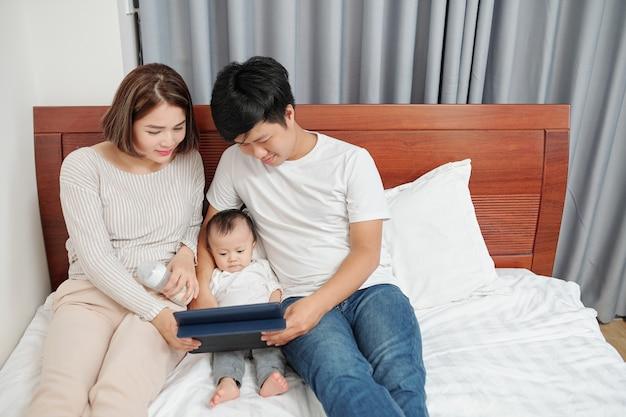 침대에서 쉬고있을 때 작은 아기에게 태블릿 컴퓨터에 만화 또는 교육 비디오를 보여주는 젊은 웃는 부모