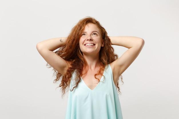 白い背景で隔離のポーズをとってカジュアルな明るい服を着た若い笑顔の物思いにふける赤毛の女性。人々の誠実な感情のライフスタイルの概念。コピースペースをモックアップします。彼女の頭の後ろで手で見上げる。
