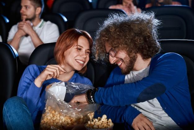 영화관에서 팝콘을 먹는 젊은 웃는 사람들.