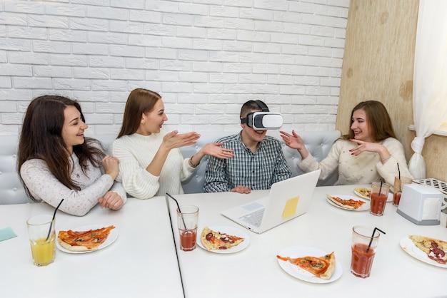 若い笑顔の人々はカフェでバーチャルリアリティデバイスを楽しんでいます