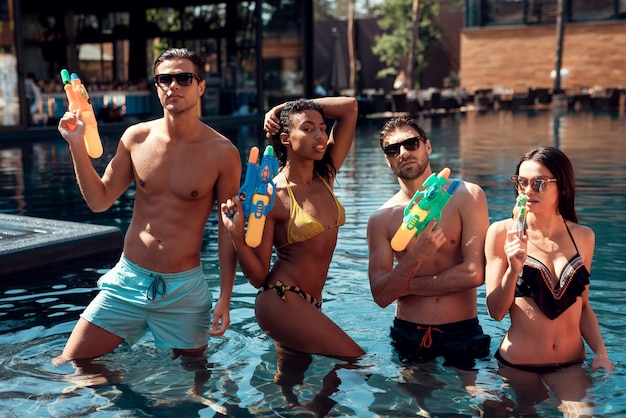 Young smiling people in pool with water guns.