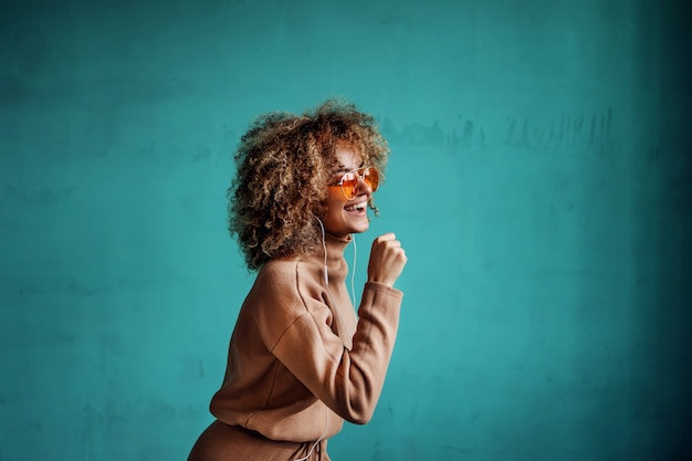 Young smiling playful fashionable woman with curly hair listening to the music and singing