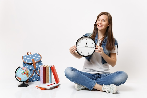 Young smiling pleasant woman student in denim clothes holding alarm clock sitting near globe, backpack, school books isolated
