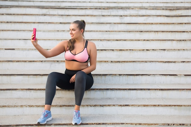 Young smiling plus size woman in sporty top and leggings sitting on stairs happily taking photo on cellphone while spending time outdoor