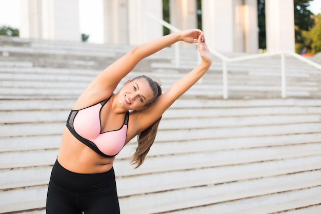 Young smiling plus size woman in sporty top and leggings stretching while happily  with white stairs