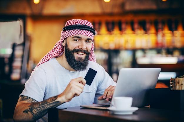 若い笑顔肯定的なひげを生やした入れ墨のイスラム教徒の男がカフェに座って、クレジットカードを保持し、オンラインで購入するものを探しています。