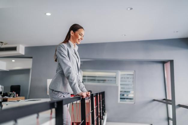 手すりに寄りかかって働いている彼女の従業員を見ているフォーマルな服装の若い笑顔の肯定的な女性チーフ。