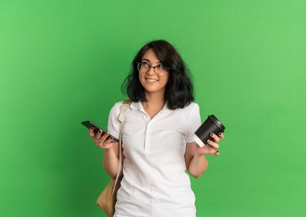 안경을 쓰고 다시 가방을 입고 젊은 웃는 예쁜 백인 여학생은 복사 공간이 녹색 측면을보고 전화와 커피 컵을 보유하고