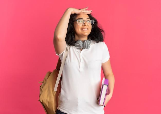 本とノートを保持している何かを見ようとしている彼女の額に手のひらを保ちながら首に眼鏡のバックバッグとヘッドフォンを身に着けている若い笑顔のかなり白人の女子高生