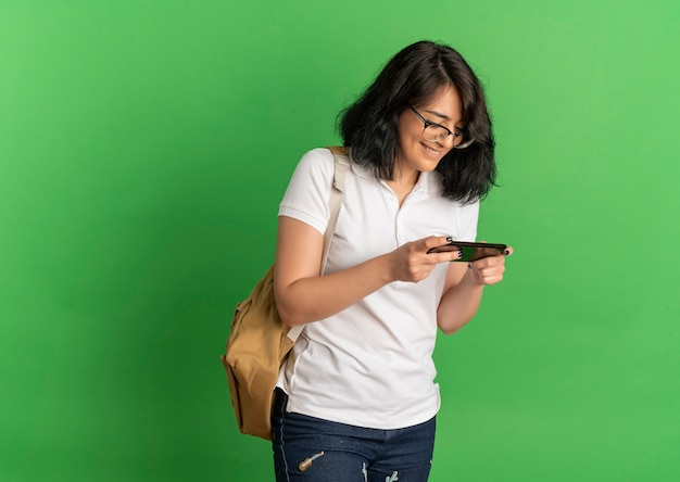 Young smiling pretty caucasian schoolgirl wearing glasses and back bag holds and looks at phone on green  with copy space