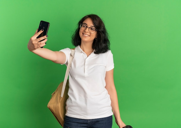Young smiling pretty caucasian schoolgirl wearing glasses and back bag looks at phone taking selfie holding coffee cup on green  with copy space