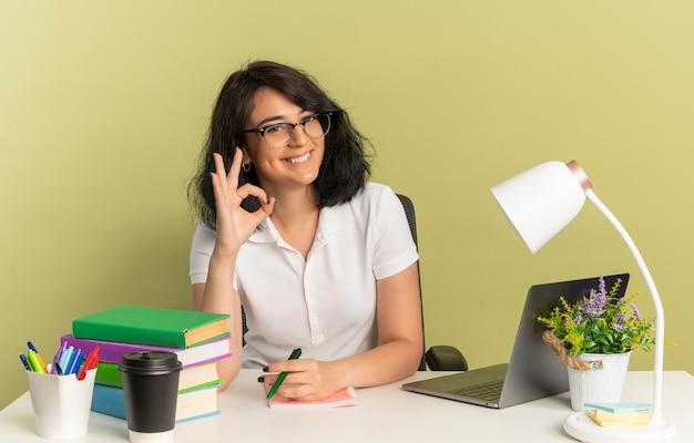 안경을 쓰고 젊은 웃는 예쁜 백인 여학생은 학교 도구 제스처 확인 손 기호로 책상에 앉아서 복사 공간이 녹색 공간에 고립 된 펜을 보유하고 있습니다.